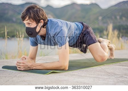 Young Man In Medical Mask Performing Some Workouts In The Park During Coronavirus Quarantine, Corona