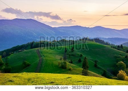 Mountainous Countryside In Springtime At Dusk. Dirt Road And Trees On The Rolling Hills. Ridge In Th