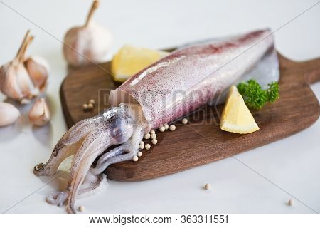 Raw Squid On Cutting Board With Salad Spices Lemon Garlic On The White Plate Background / Fresh Squi