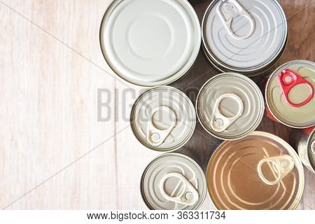 Various Canned Food In Metal Cans On Wooden Background , Top View / Canned Goods Non Perishable Food