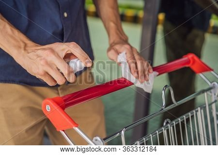 Man Hand Disinfecting Shopping Cart With Alcohol Spray For Corona Virus Or Covid-19 Protection