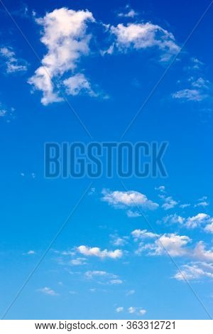 Bright Fluffy Clouds On The Blue Sky. Wonderful Nature Background In Summertime