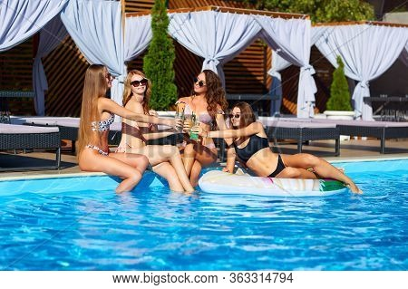 Happy Attractive Women In Bikini Have Fun On Poolside Summer Party Drinking Fresh Colorful Cocktails