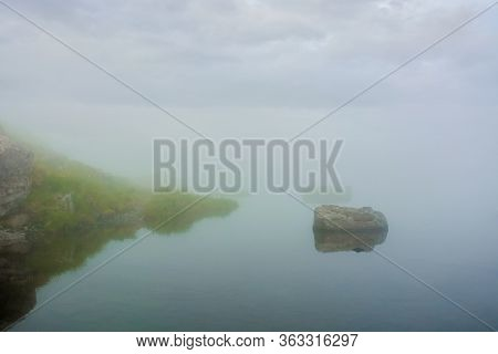 Fog On The Lake. Grassy Shore With Rocks. Overcast Sky. Mysterious Nature. Poor Visibility Concept