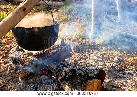 Steaming Old Pot Outdoor. Cooking And Camping. Outdoor Adventures Concept. Beaten Cauldron On Camp F