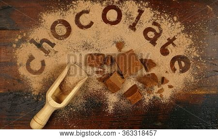 The Word Chocolate Spelled Into Chocolate Powder On Dark Wood Vintage Table.