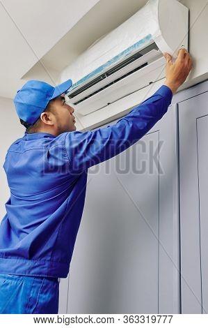 Repairman In Uniform Checking Broken Air Conditioner In House Of Customer