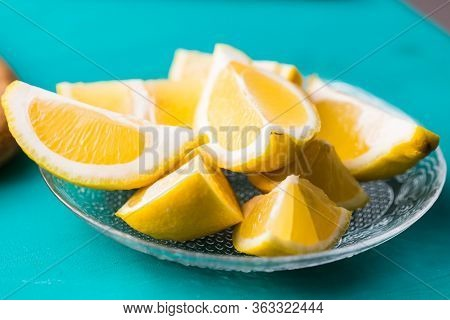 Lemon Wedges On The Plate - Lemon Wedges Or Slices On A Turquoise Background.
