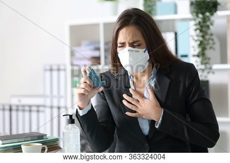 Executive Woman Wearing Protective Mask With Asthma Attack Holding Inhaler Touching Chest At The Off
