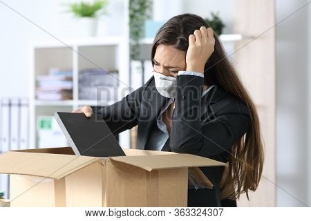 Sad Fired Executive Woman With Protective Mask Packing Personal Belongings On A Box At The Office