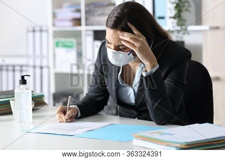 Worried Executive Woman Wearing Mask Signing Contract At The Office