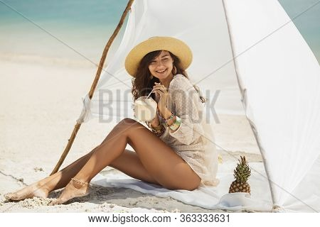 Woman With Coconut Drink Resting On The Beach Near The Water. Summer Holiday Idyllic. Happy Young Sl