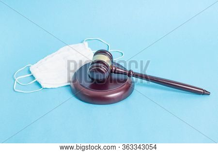 Judicial Gavel And Protective Medical Mask On A Blue Background. Concept Of Illegal Resale Of Protec