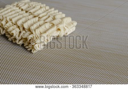 Instant Vermicelli On A Beige Background. Close-up Rectangle Of Dry Instant Noodles. Fast Junk Food.