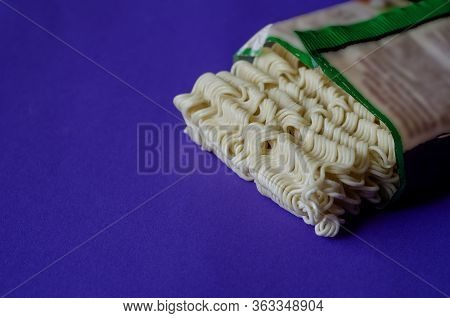 Uncooked Instant Noodles To Open The Wrapper.rectangle Of Dry Instant Noodles On A Blue Background.