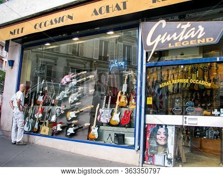 Paris, France - July 7, 2006: A Young Man Looks At Shop Window Of Guitar Legend Selling New And Used