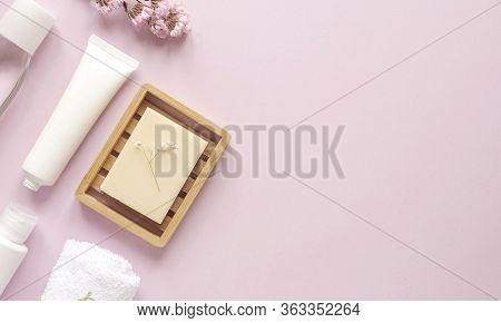 Care Products Lotion, Cream, Plant, Towel. Bath Accessories On Pink Background, Top View, Copyspace,