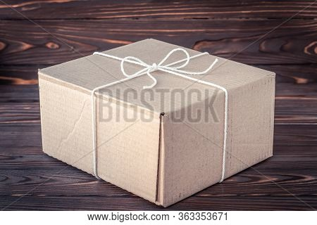 Gift Box On Dark Brown Wooden Background. Parcel Delivery Service Concept, Shipping In Quarantine Fr