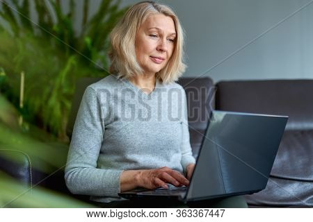 Serious Woman Using Laptop Checking Email News Online Sitting On Sofa, Searching For Friends In Inte