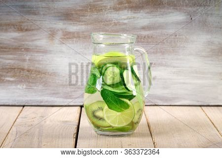 Lemonade Drinks With Slices Of Lime On The Glass, And Carafe. Slices Of Lime, Ice And Mint Leaves On