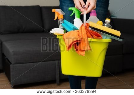 A Girl Is Holding Detergents In A Bucket On The Background. Woman Is Ready To Clean House. Cleaning