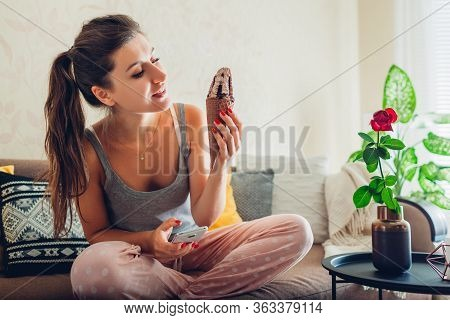Young Woman Eating Chocolate Ice-cream In Cone Lying On Couch At Home And Using Smartphone. Relaxing