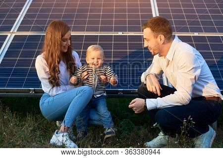 Young Family Of Three Is Crouching Near Photovoltaic Solar Panel, Little Boy Is Looking At Camera, P