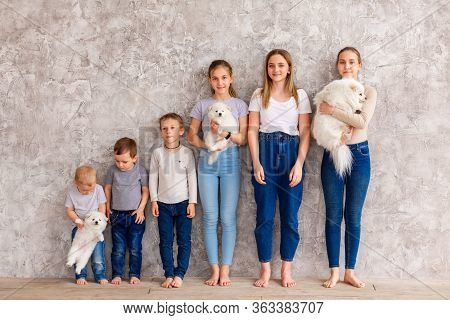 Happy Children Of Different Age With Puppies Standing In Line