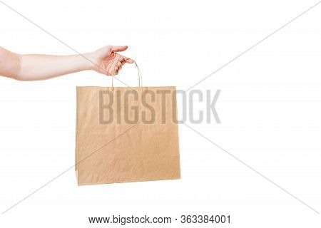Hand Holds Brown Eco Friendly Craft Paper Bag, Label Packet For Grocery Delivery And Merchandise Iso