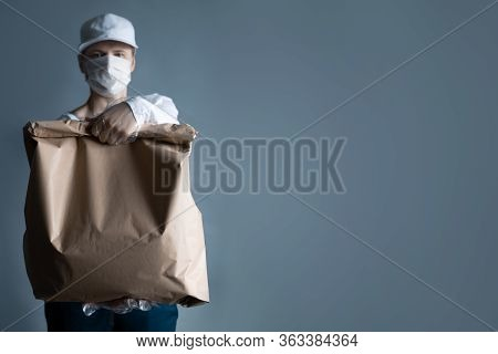 Safe Food Or Goods Delivery. Young Courier Delivering Grocery Brown Eco Paper Bag Order To The Home