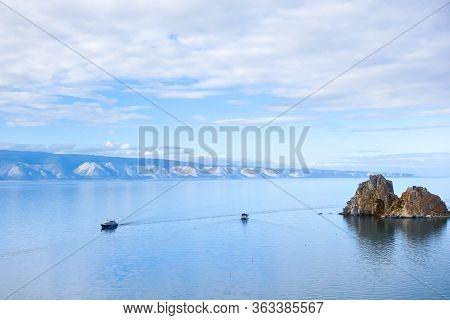 Two Pleasure Tourist Boats Sail On The Water Of Lake Baikal. Cape Burhan Near The Island Of Olkhon,