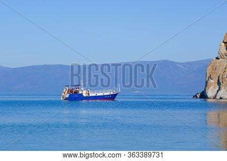 A Pleasure Tourist Boat Floats On The Water Of Lake Baikal. Rocky Cape Burhan Near The Island Of Olk