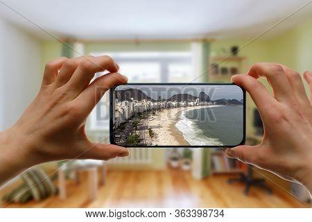 Online Travel To Copacabana Beach In Rio De Janeiro, Brazil. Using A Smartphone At Home.