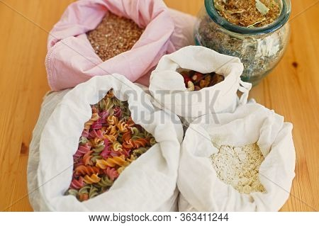 Groceries In Reusable Textile Bags On Wooden Table. Cereals,pasta, Flour, Grains In Bags, Tea In Gla
