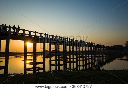 Silhouette of U Bein bridge with reflection in water at sunset with sunrays shining under bridge in Amarapura, Mandalay, Myanmar