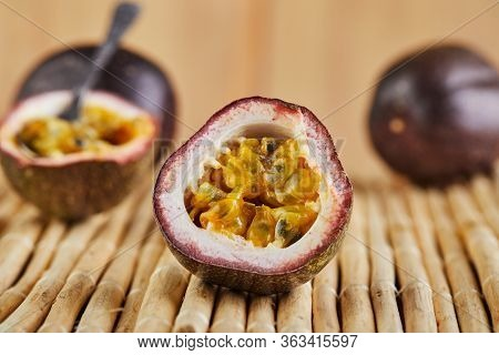 Passiflora Is Cut Into Two Halves With A Spoon Inside And Two Whole On A Bamboo Background. Side Vie