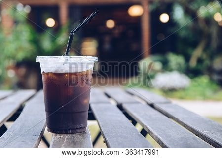 A Plastic Cup Of Iced Americano (black Coffee) Serving On The Wood Plank Table. The Iced Americano I