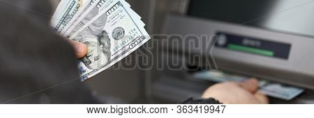 Man Stand Near Terminal And Withdraws Cash Dollars. Limit Cash Withdrawals During Quarantine. Automa