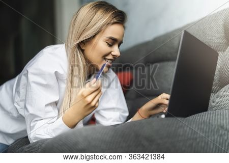 Beautiful Blonde Woman Using Bank Card To Pay For Goods Purchased Online. Safe Payment Services For