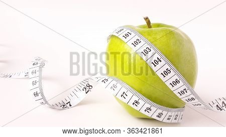 Fresh Green Fruits Wrapped In A Measuring Tape.concept Of The Goal To Lose Weight,the Goal Of Diet