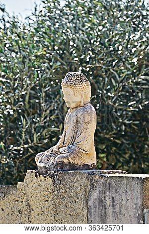 Vesak Day Is Buddhas Birthday. Little Buddha Statue On Fence In Olive Garden