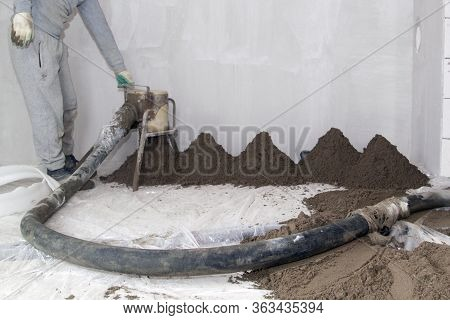 Machine Running Screed Flooring. Worker At Construction Site Sand And Cement Floor Screed. Machine A