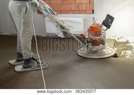 Craftsman Performing And Polishing Sand And Cement Screed Floor On Construction Site Of New Apartmen