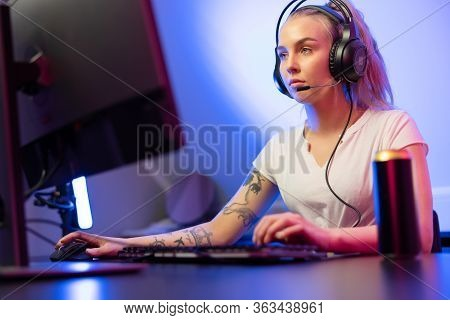 Professional Gamer Girl With Headset Play Online Multiplayer Video Game On Pc