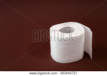 A Roll Of Toilet Paper On A Brown Background. Copy Space. Space For Text.