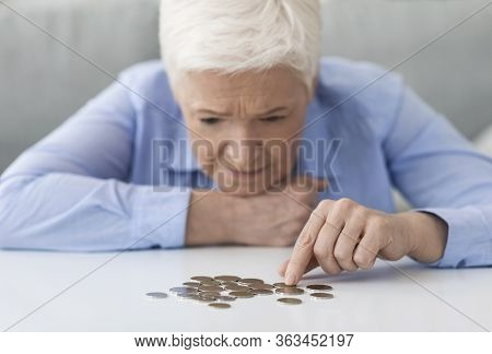 Coronacrisis And Financial Problems. Senior Woman Counting Remaining Coins On Table, Suffering From