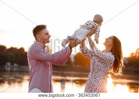 Beautiful Woman Lifts High Her Adorable Baby Girl Up Mid Air And Looks At Her Smiling. Happy Parents