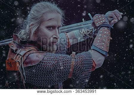 Portrait of a brave medieval warrior in armor with a sword on a black background with snowfall. The Witcher man.