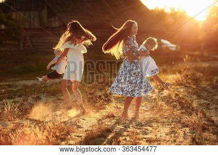 Happy Young Moms Playing With Their Kids Outdoors In Summer. Happy Family Time Together Concept. Sel