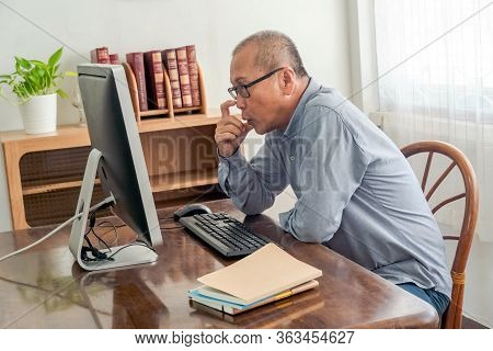Middle Age  Man Sitting In The House And Using  Computer For Online Working At Home When Self Quaran
